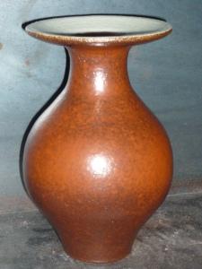 Bouteille à col plat en grés , interieur rouge de fer (kaki) , bord engobe jaune , exterieur rouge de fer (kaki) . Hauteur 17.5 cm , diametre col 10.5 cm diametre base 5 cm .